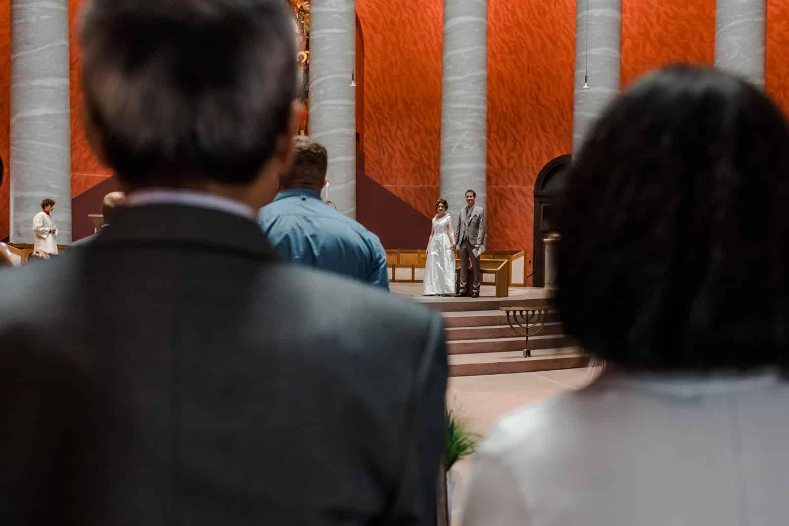 Brautpaar steht mit Gästen in der St. Ludwig Kirche in Darmstadt.