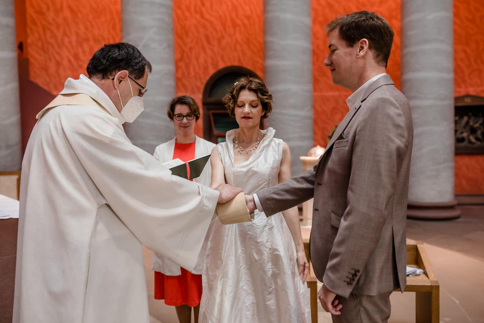 Pfarrer segnet ein Brautpaar in der St. Ludwig Kirche in Darmstadt während der Coronazeit mit Mundschutz.