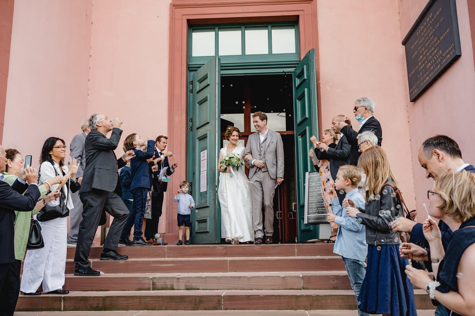 Brautpaar kommt aus der St. Ludwig Kirche in Darmstadt und die Gäste blasen Seifenblasen.