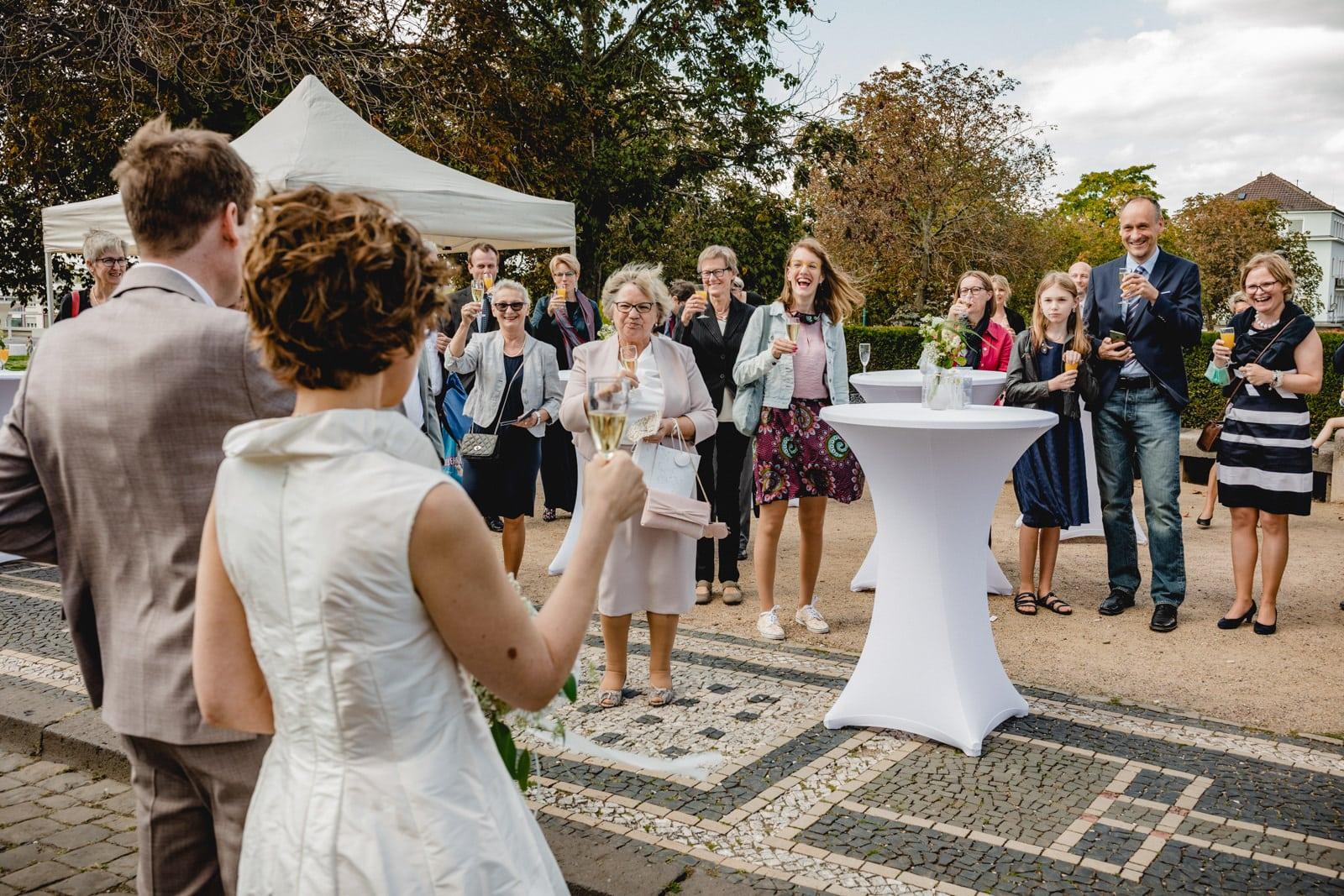 Brautpaar steht vor Hochzeitsgesellschaft und Prostet vor der St. Ludwigskirche in Darmstadt