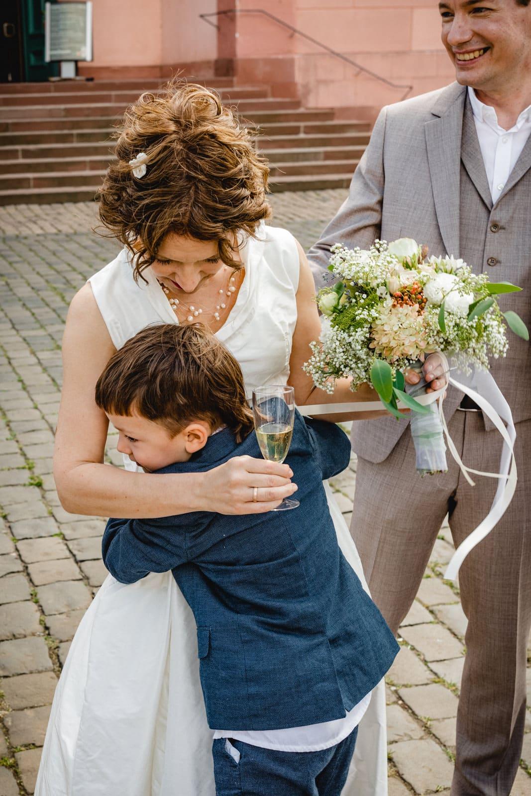 Ein Junge umarmt eine Braut vor der St. Ludwigskirche in Darmstadt nach der Trauung.