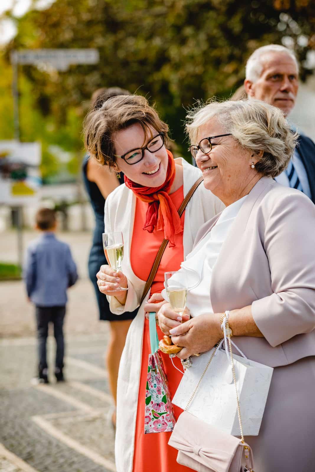 Zwei Frauen lachen mit Sekt in der Hand draussen vor der St. Ludwigs Kirche in Darmstadt während des Sektempfangs.
