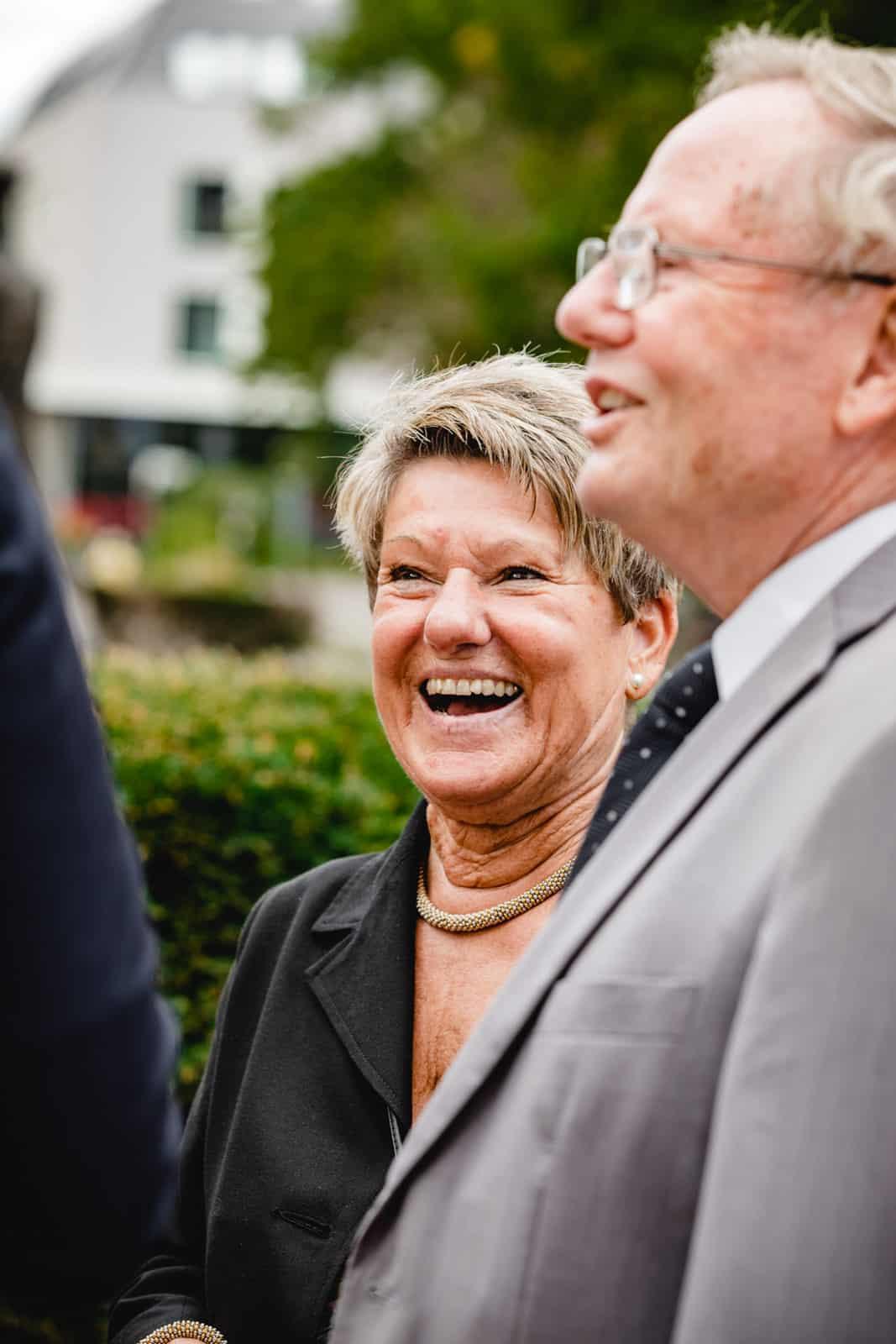 Frau lacht draussen vor der St. Ludwigs Kirche in Darmstadt während des Sektempfangs.