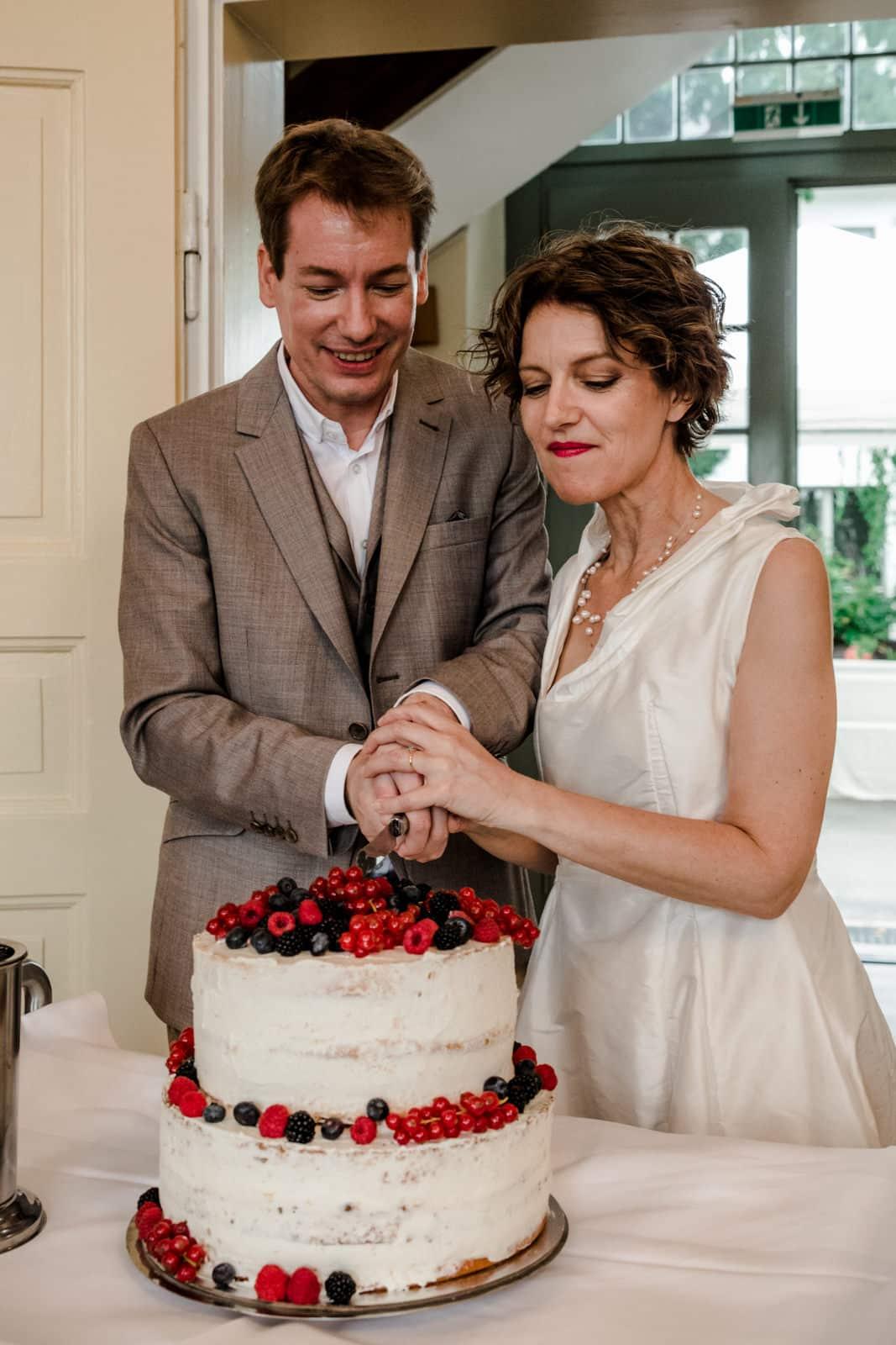 Brautpaar schneidet eine zweistöckige Hochzeitstorte mit Beeren im Vintagestil Prinz-Emil-Schlösschen in Darmstadt an.
