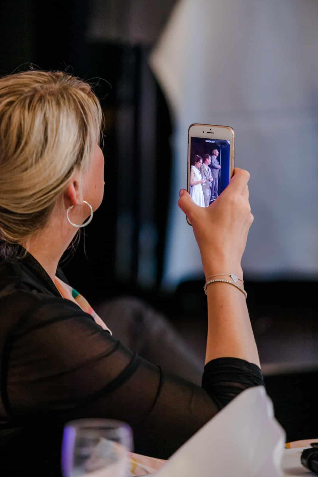 Eine Frau nimmt die Rede des Brautvaters mit dem Handy auf Prinz-Emil-Schlösschen in Darmstadt.