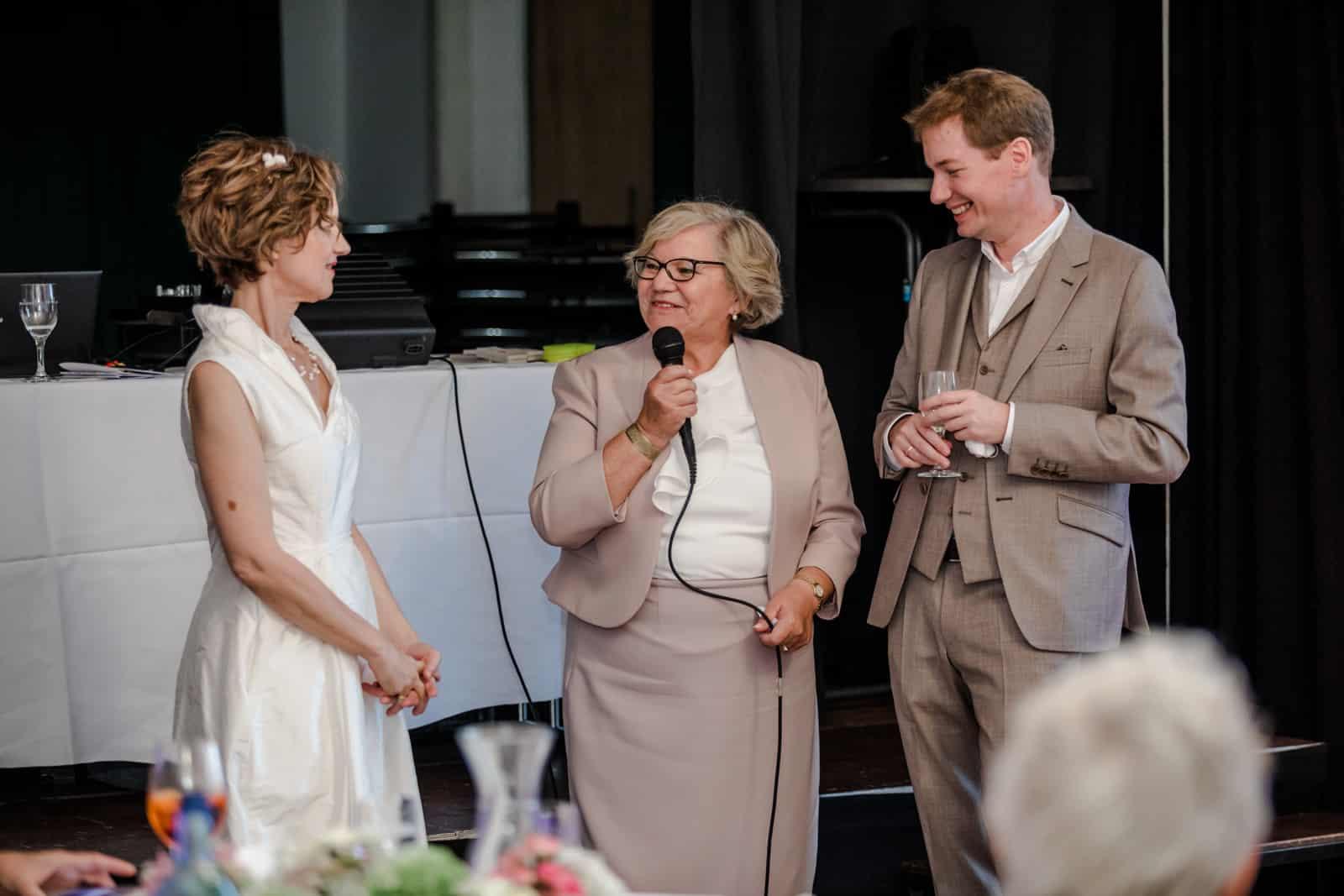 Brautmutter hält Hochzeitsrede zu ihrer Schwiegertochter und Mann lacht mit Glas in Hand im Prinz-Emil-Schlösschen in Darmstadt.