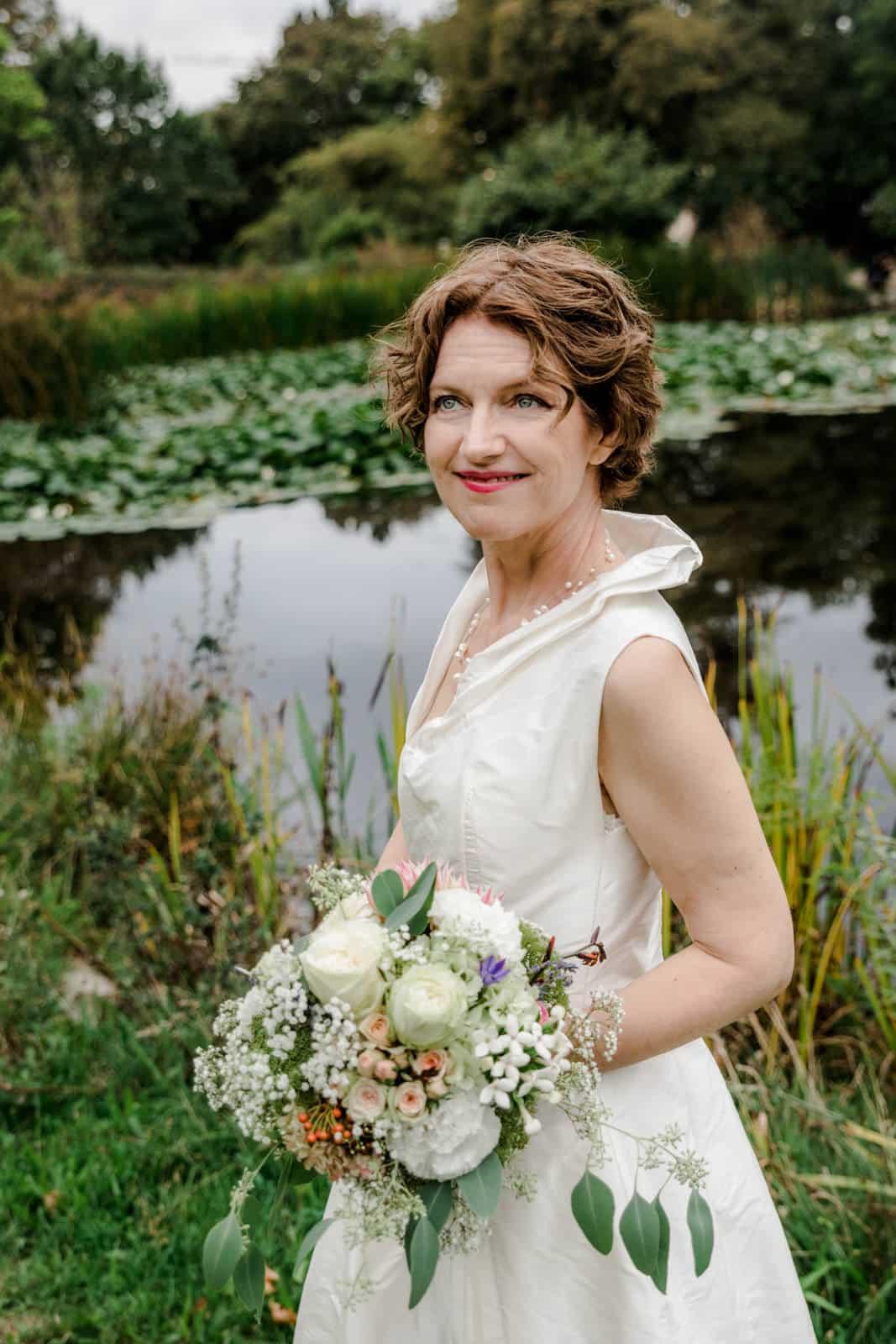 Braut steht am See im Park des Prinz-Emil-Schlösschen in Darmstadt und lacht zu ihrem Mann