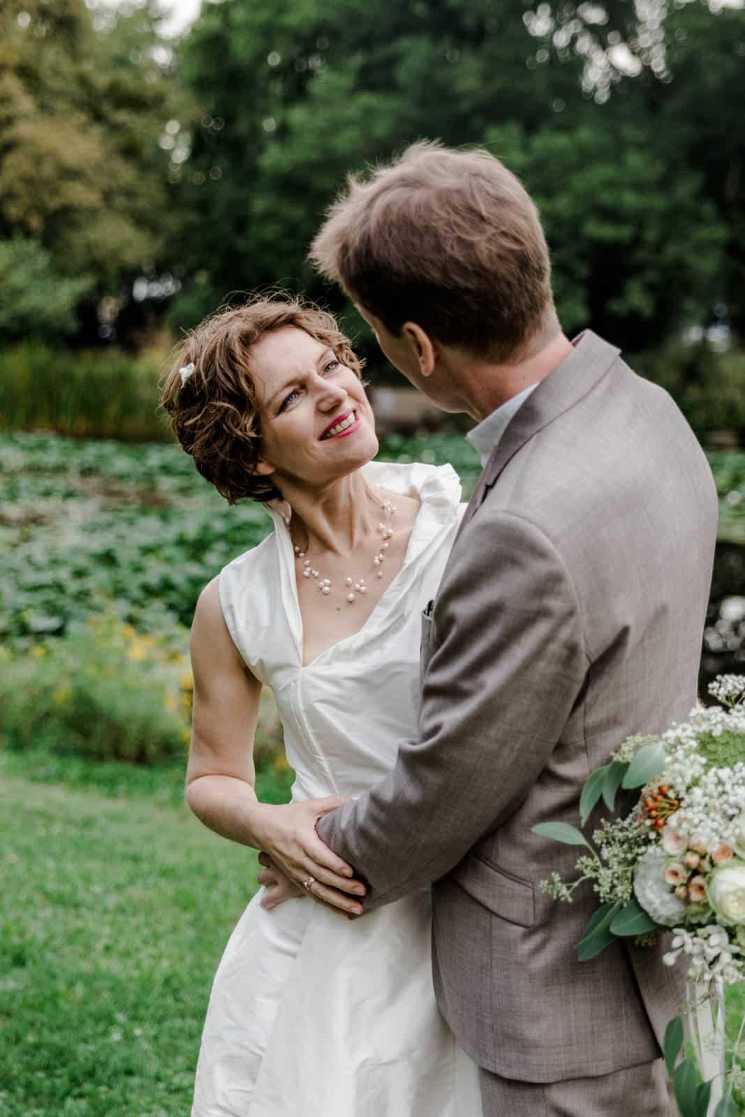 Braut lacht ihren Mann bei Brautpaarshooting im Park des Prinz-Emil-Schlösschen in Darmstadt an