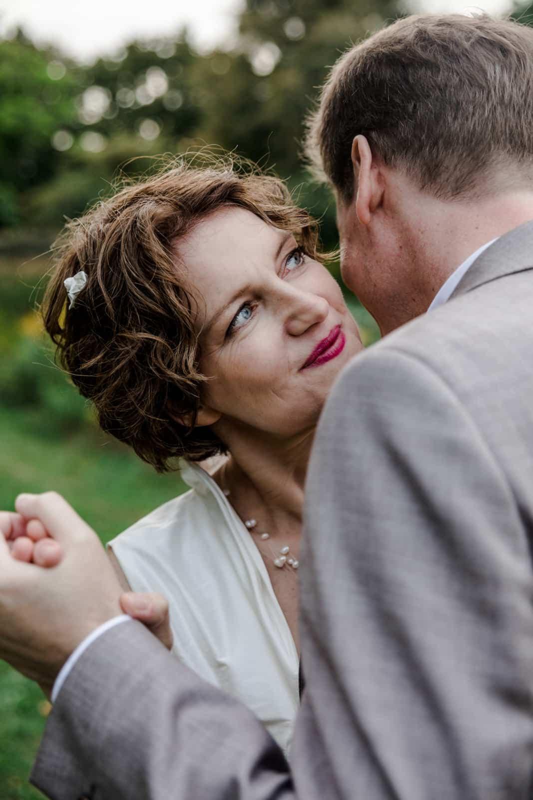 Bräutigam flüstert seiner Braut etwas ins Ohr im Park des Prinz-Emil-Schlösschen in Darmstadt