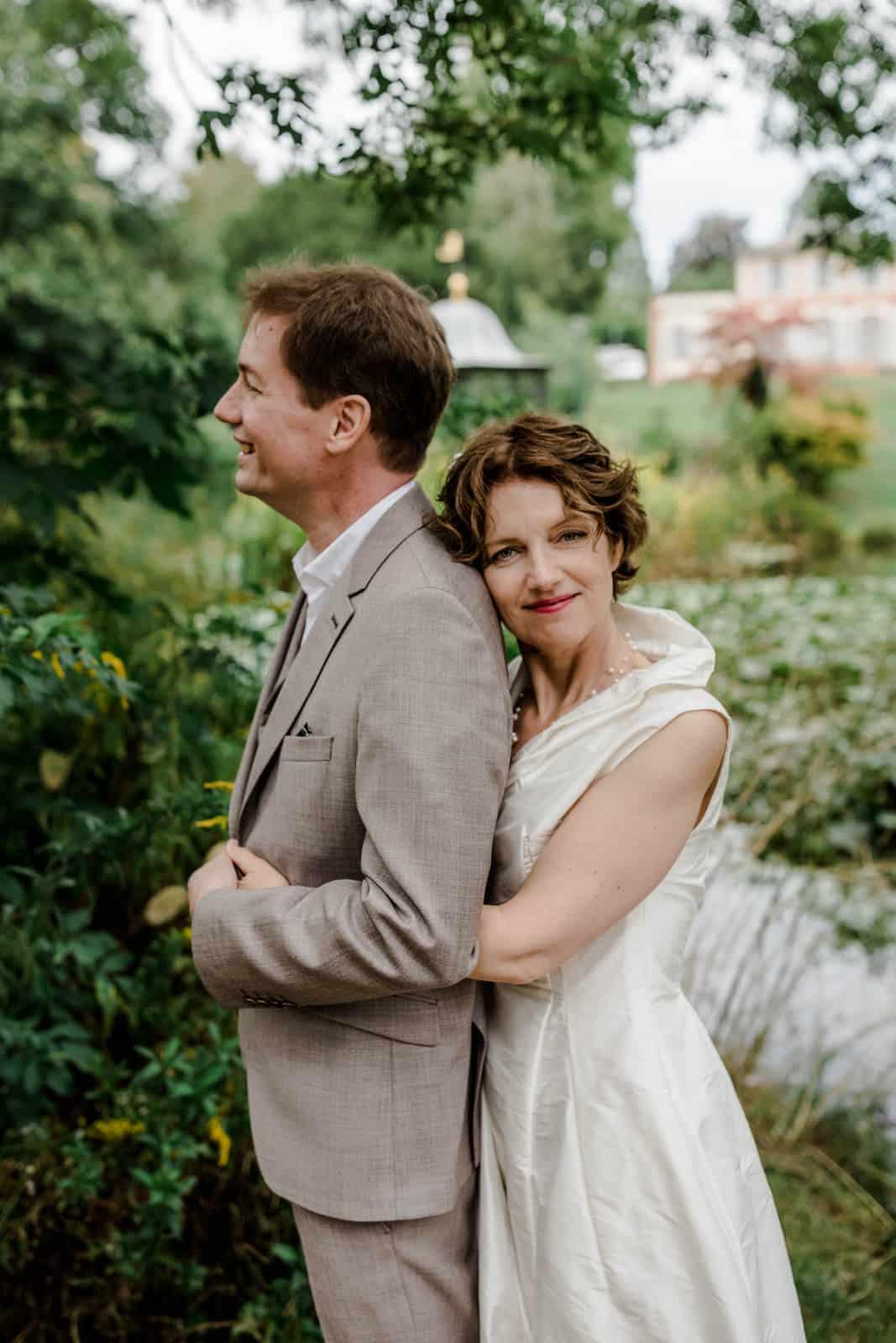 Braut kuschelt sich an die Schulter ihres Mannes im Park des Prinz-Emil-Schlösschen in Darmstadt