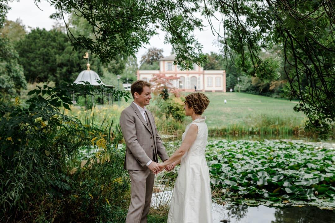 Brautpaar steht Hand in Hand am See im Park des Prinz-Emil-Schlösschen in Darmstadt und lacht sich an.