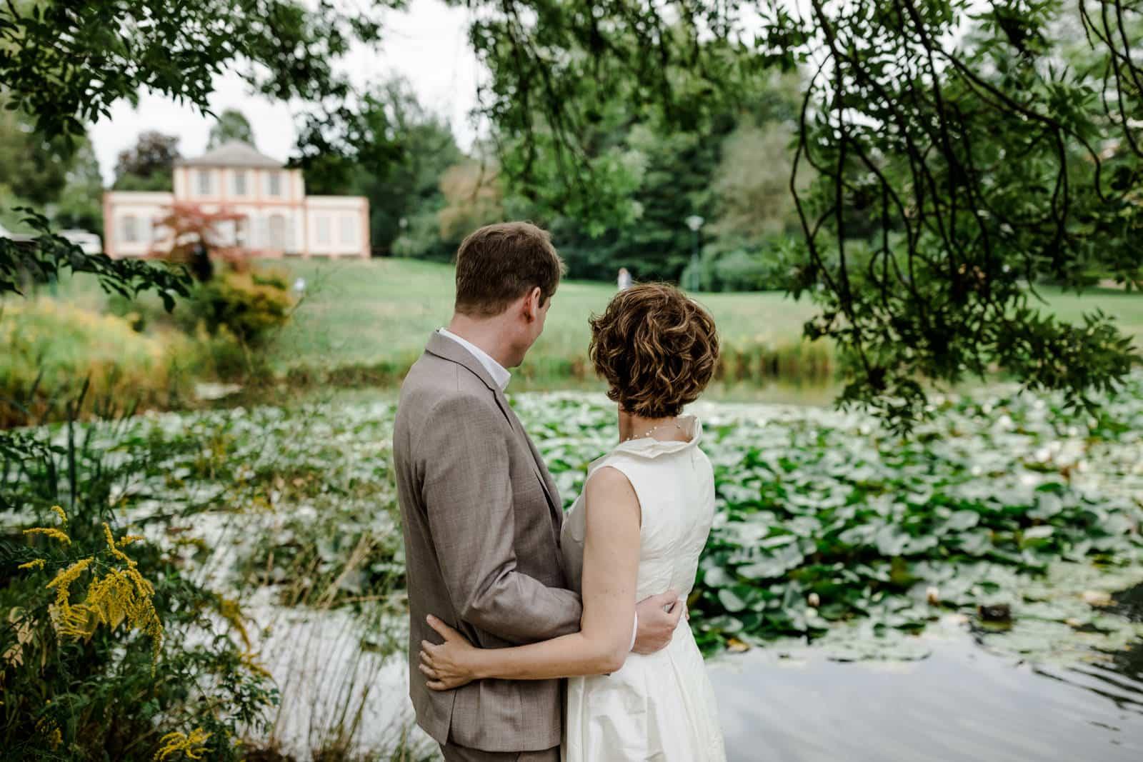 Brautpaar steht Arm in Arm am See im Park des Prinz-Emil-Schlösschen in Darmstadt und schaut dorthin.