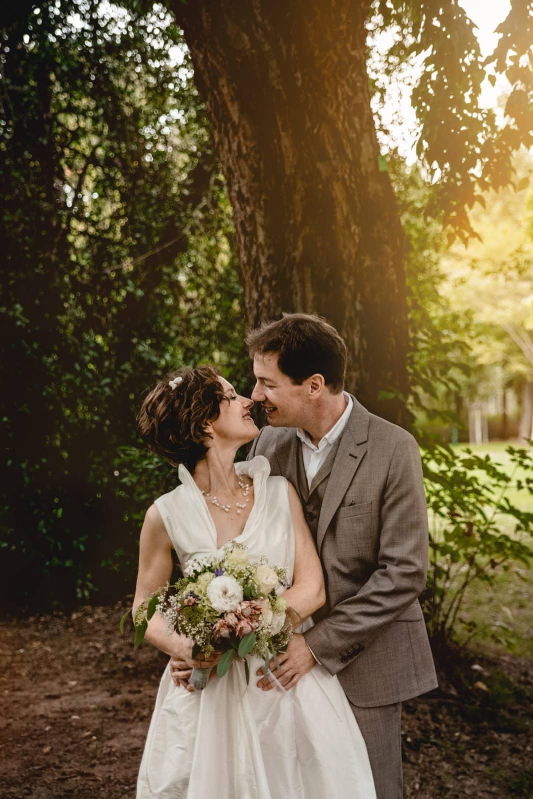 Brautpaar steht unter einem Baum bei Sonnenschein und ist kurz davor sich zu küssen im Park des Prinz-Emil-Schlösschen in Darmstadt