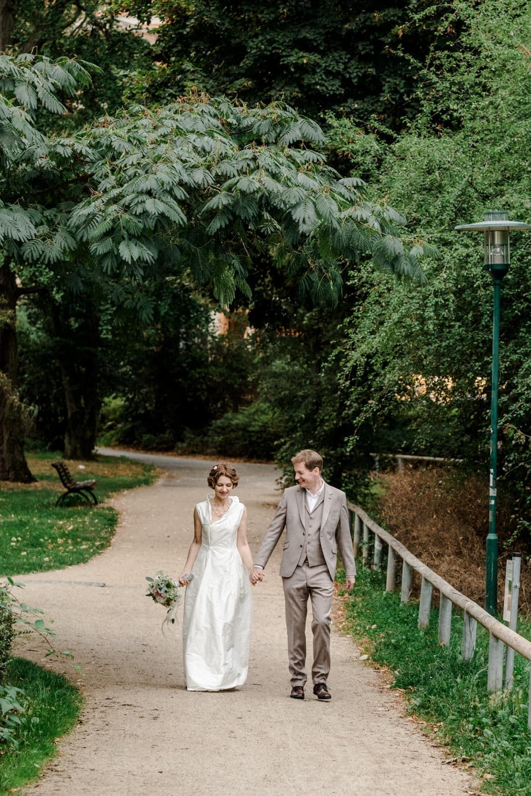 Brautpaar läuft Hand in Hand im Park des Prinz-Emil-Schlösschen in Darmstadt