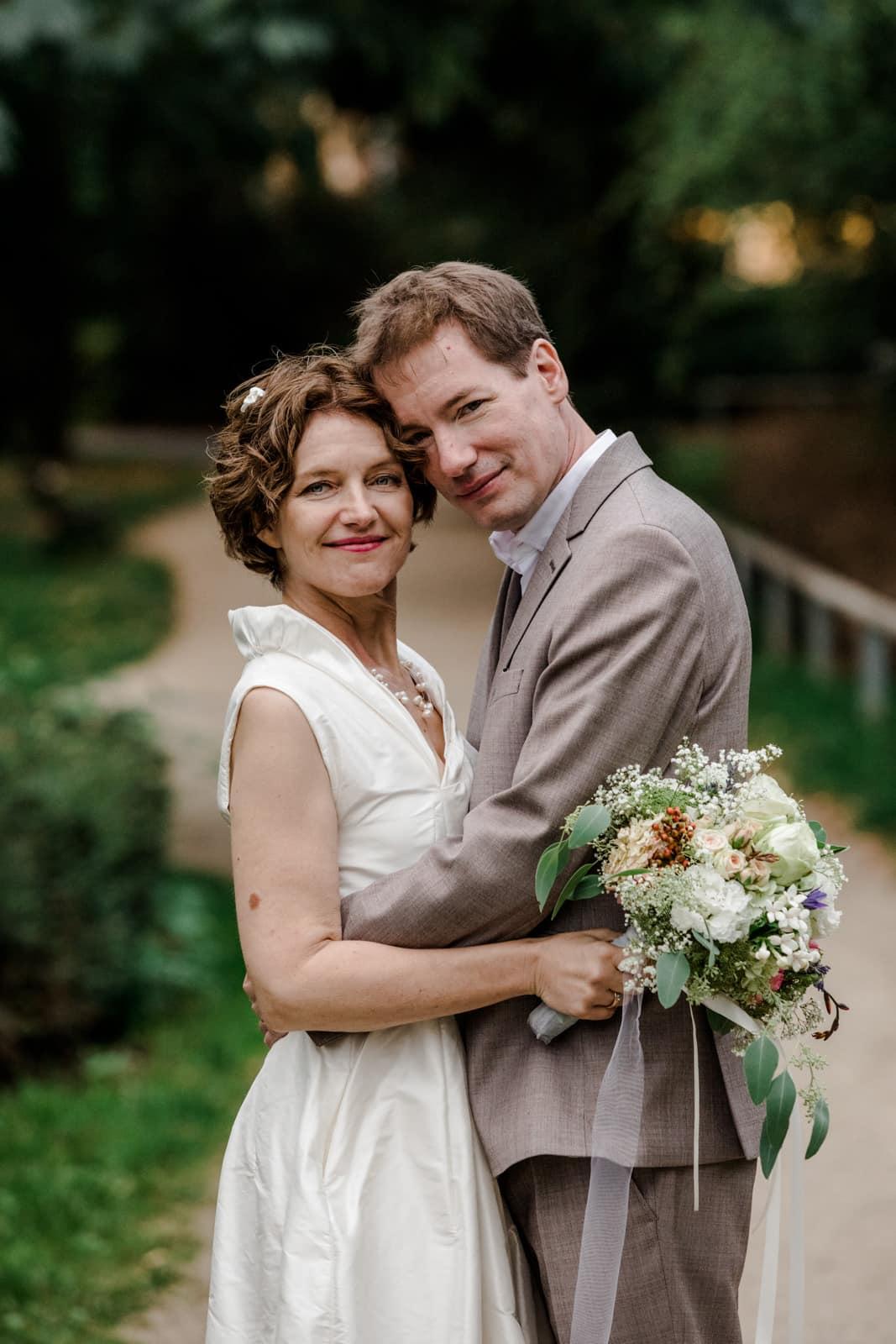 Brautpaar steht in der grünen Natur in Brautkleidung Kopf an Kopf im Park des Prinz-Emil-Schlösschen in Darmstadt.