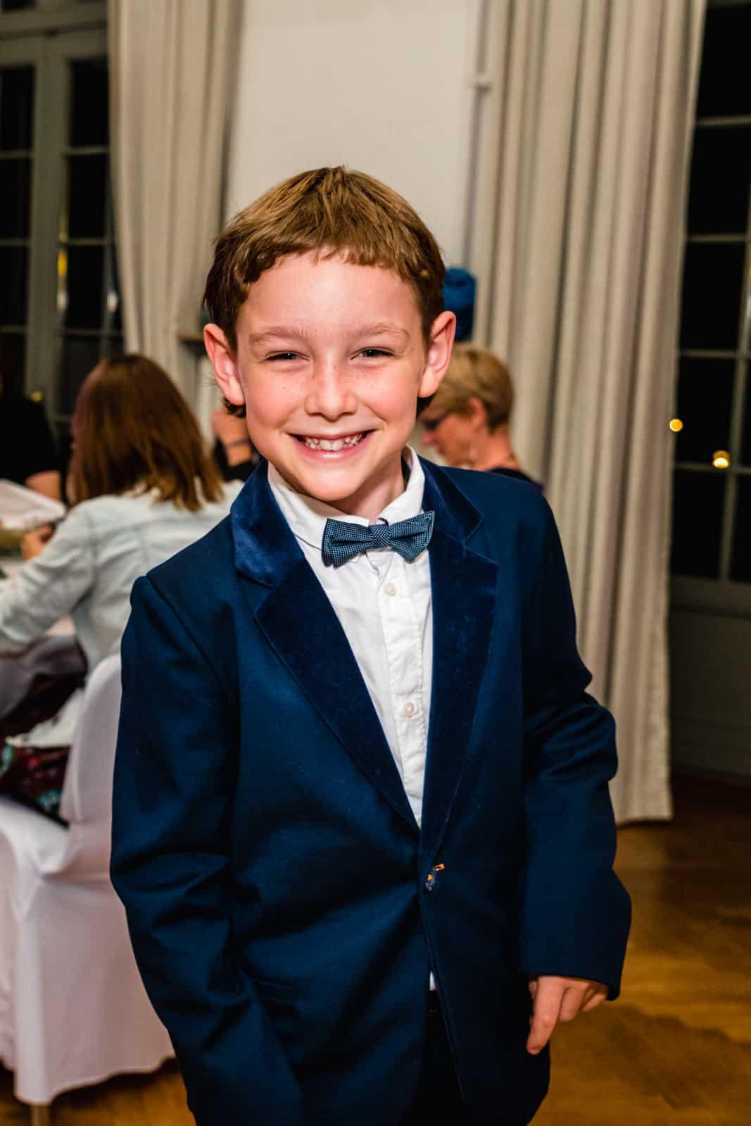 Ein Junge lacht bei einer Hochzeit in die Kamera und hat einen blauen Anzug an im Prinz-Emil-Schlösschen