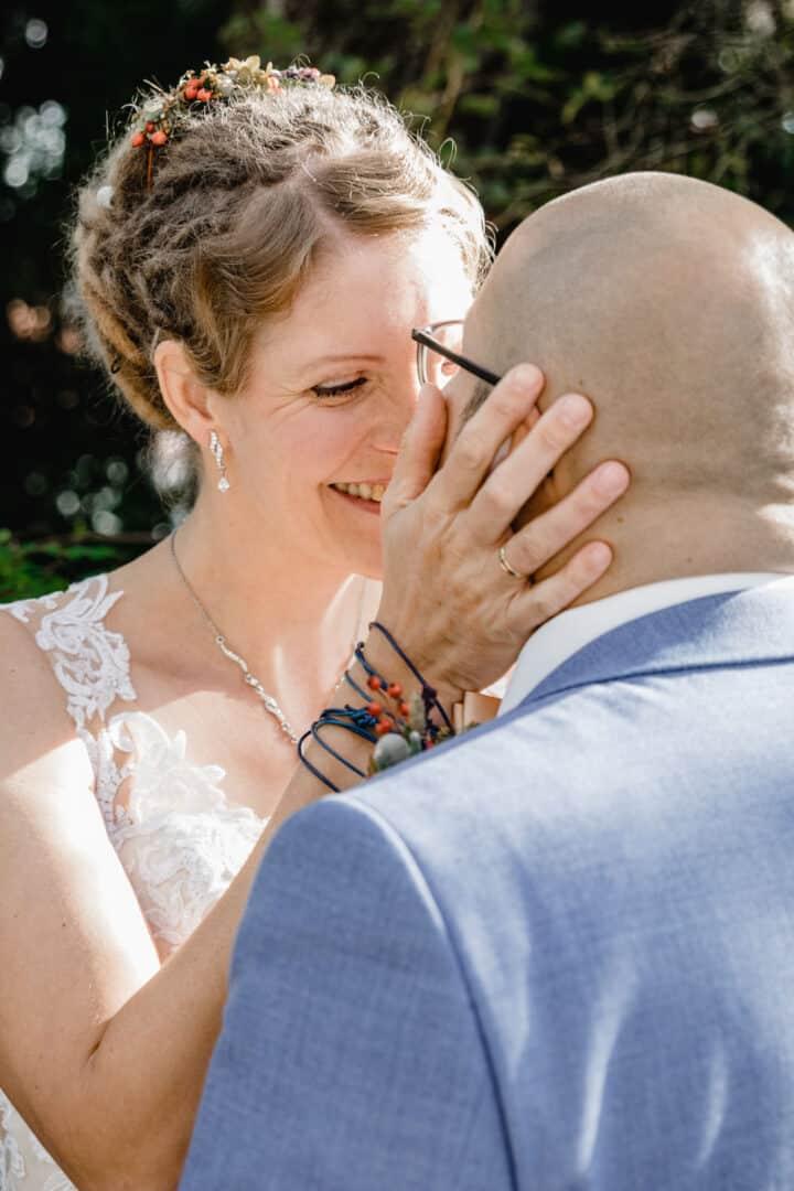 Braut hält den Kopf ihres Mannes und küsst ihn