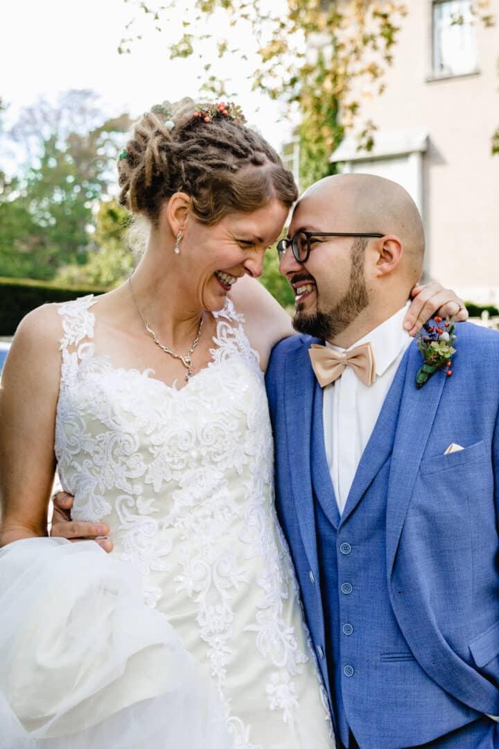 Brautpaar läuft auf Straße entlang und lacht sich an mit Kopf an Kopf gelehnt