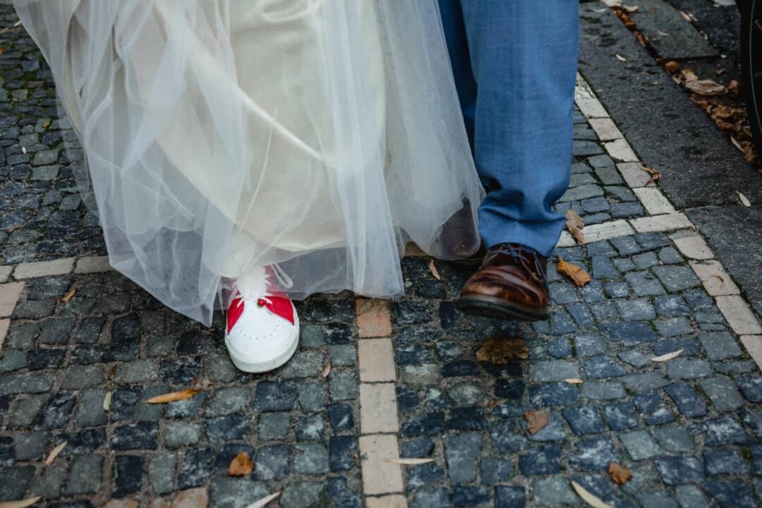 Brautpaar läuft die Pflasterstraße entlang und man sieht die Schuhe