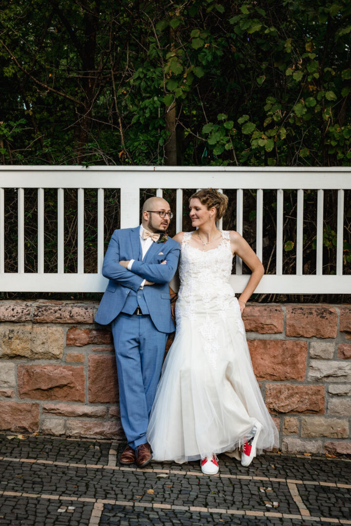 Brautpaar lehnt an Mauer des Vortex Garten in der Stadt und lacht sich an