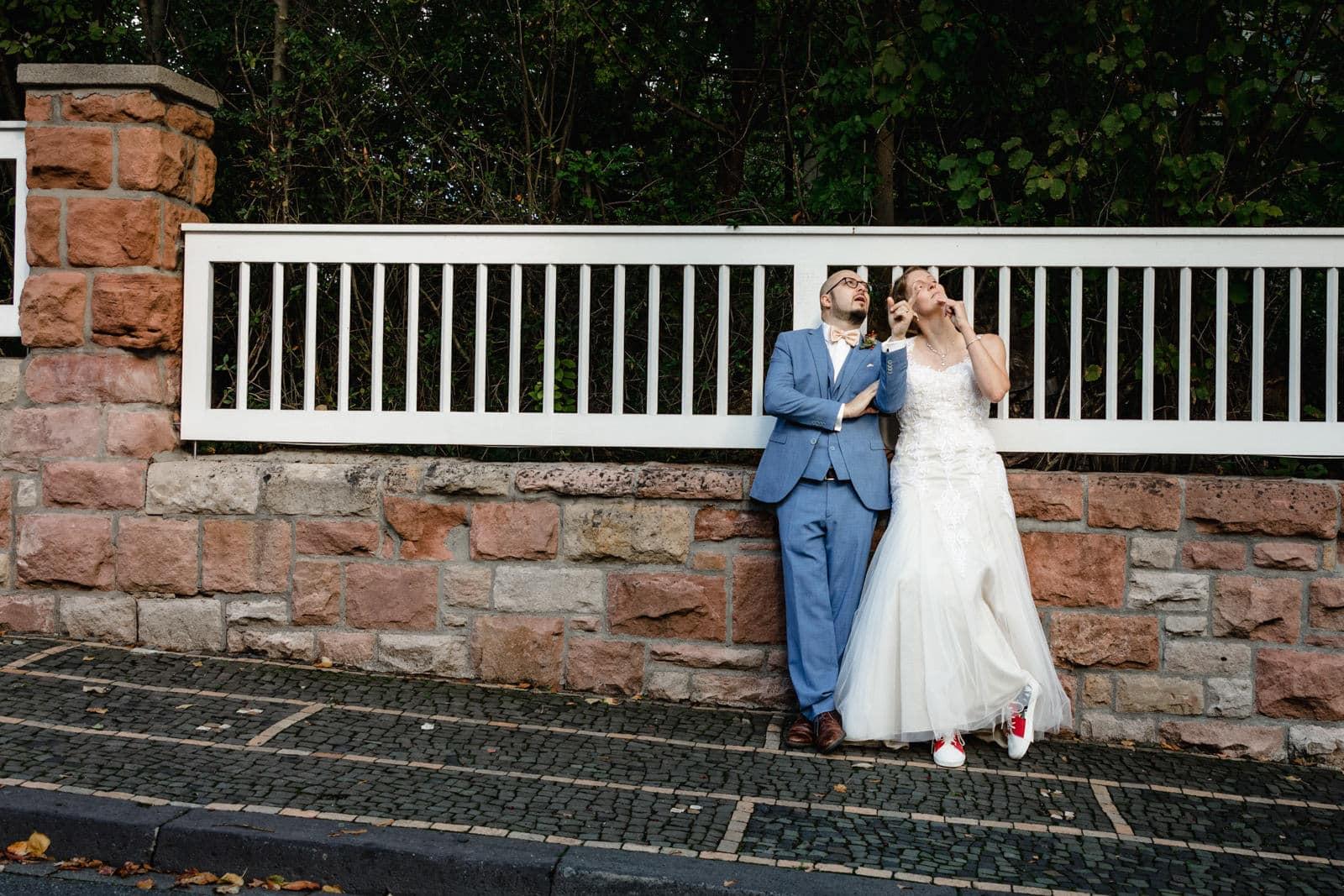 Hochzeitspaar steht an der Mauer des Vortexgarten gelehnt und schaut in die Luft