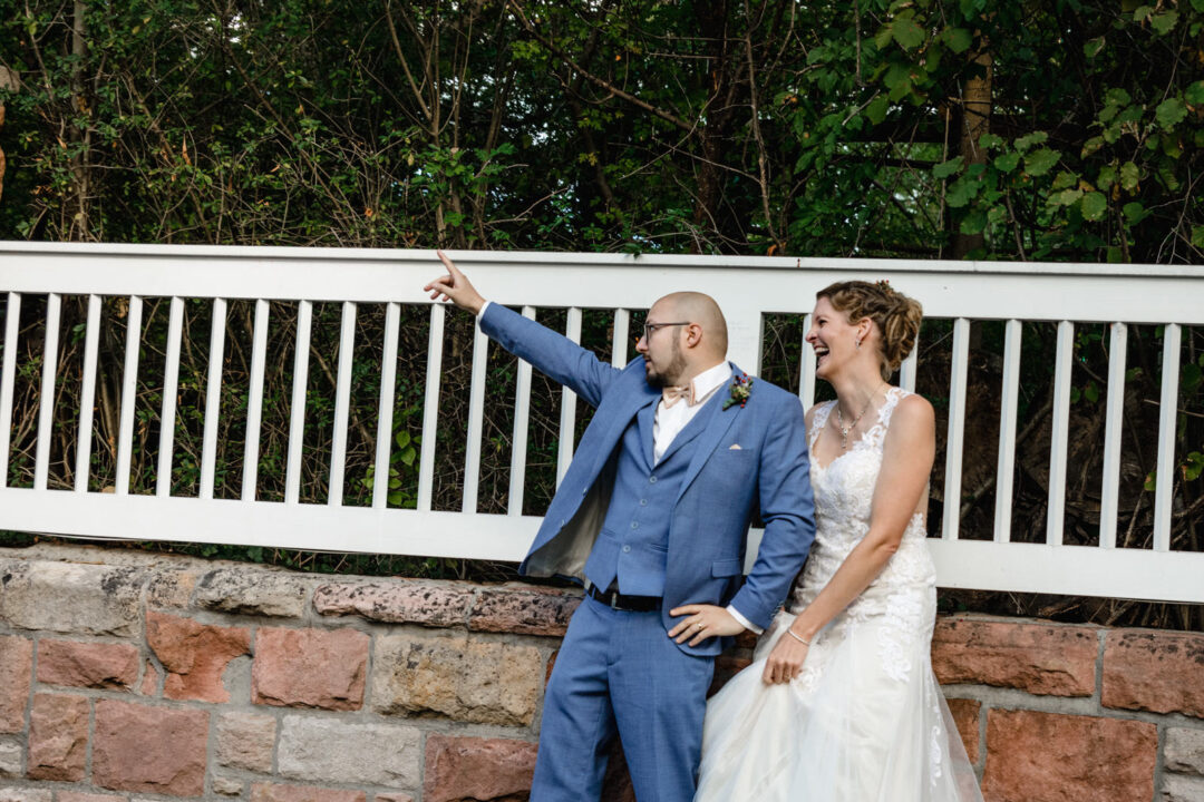 Brautpaar steht an Mauer und macht blödsinn