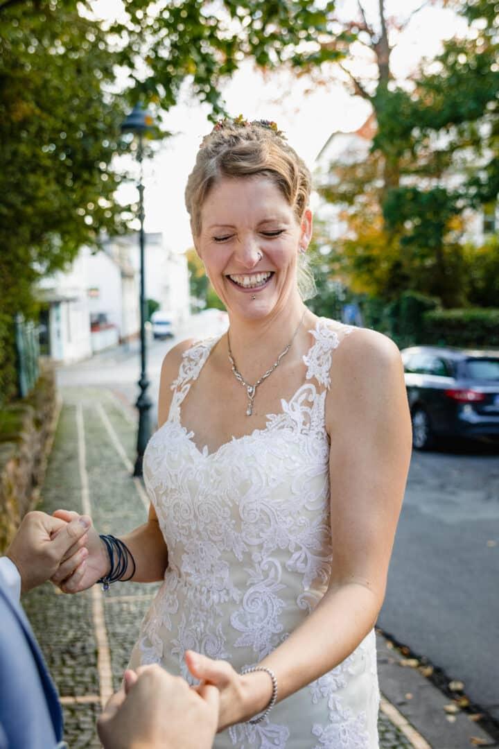 Braut lacht herzlich und hält Ehemann an der Hand