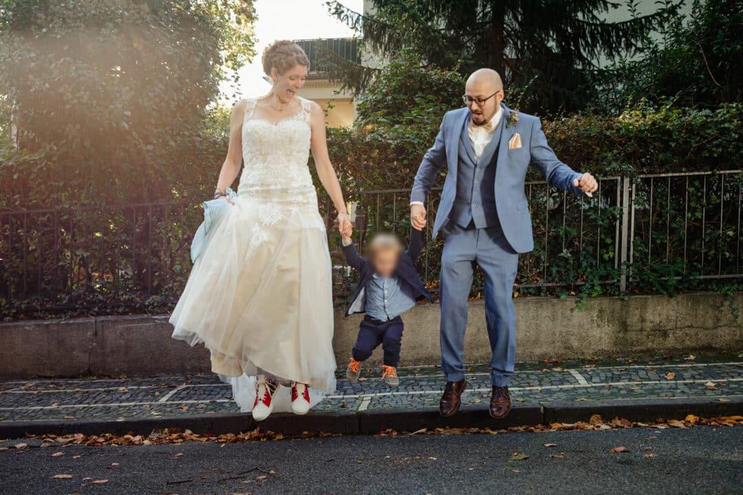 Brautpaar hüpft mit kleinem Sohn an der Hand von Bordsteinkante