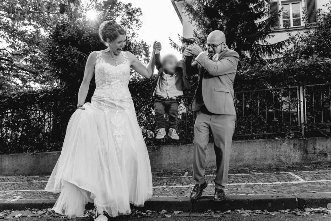 Brautpaar hat kleinen Sohn in der Mitte an der Hand und springt mit ihm von Bordsteinkante