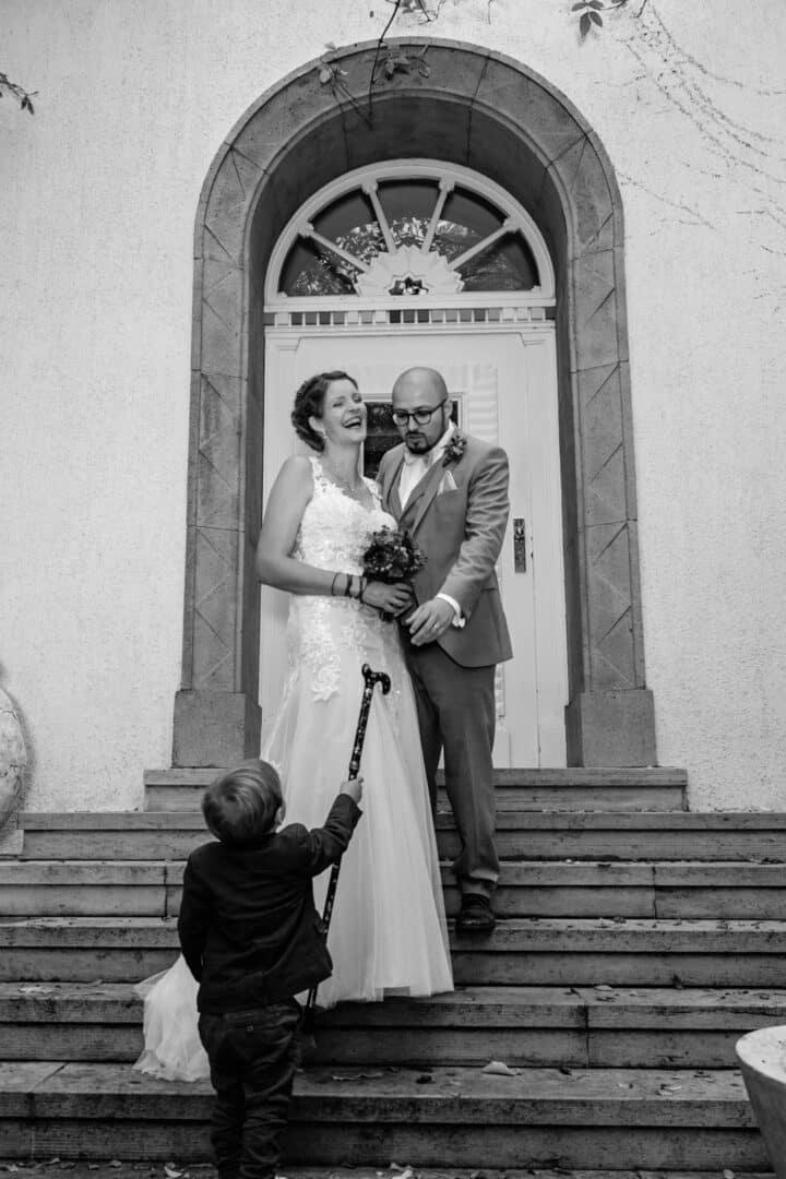 Brautpaar steht auf Treppe im Vortex garten und lacht weil Sohn einen Gehstock bringt