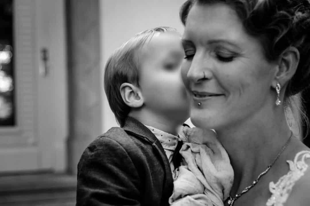 Junge küsst Mama auf die Wange
