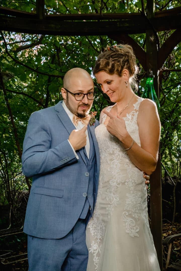 Brautpaar steht zusammen und deutet mit den Fingern