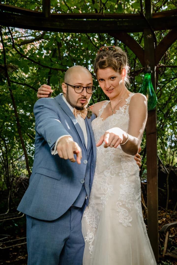 Brautpaar deutet mit Finger auf Kind