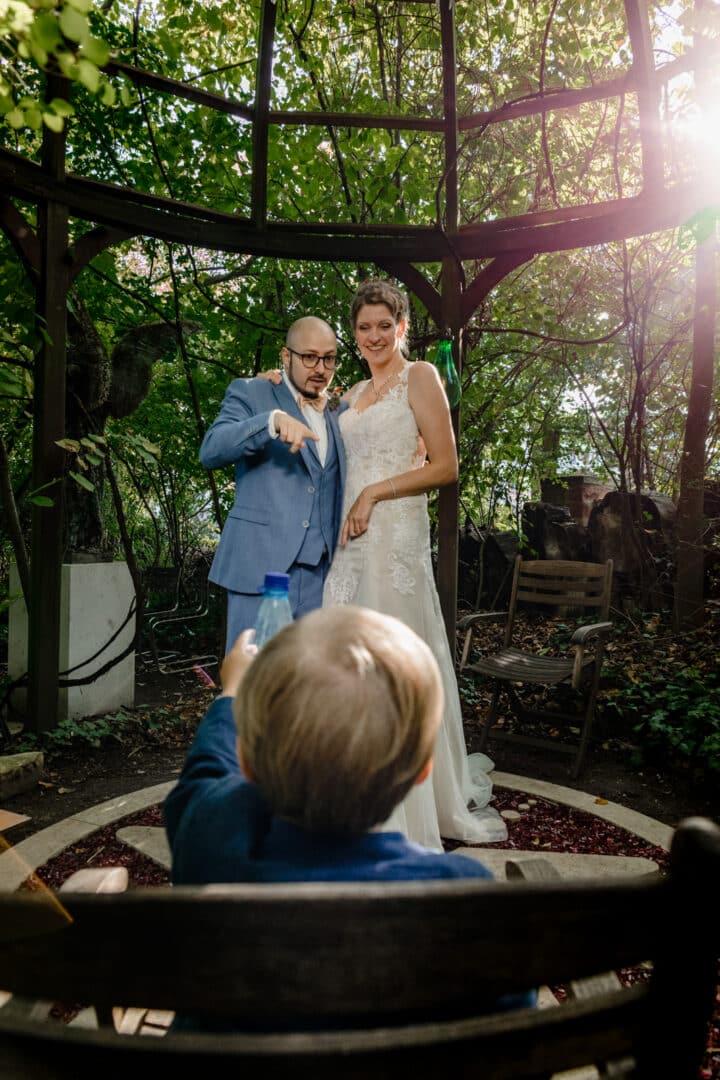 Brautpaar lacht und zeigt auf Sohn der auf einem Stuhl sitzt
