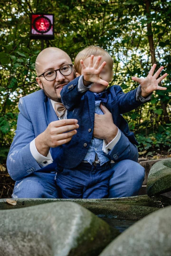 Ehemann hält Sohn fest der vor einem kleinen Wasserfall steht und die Hände nach vorne hält