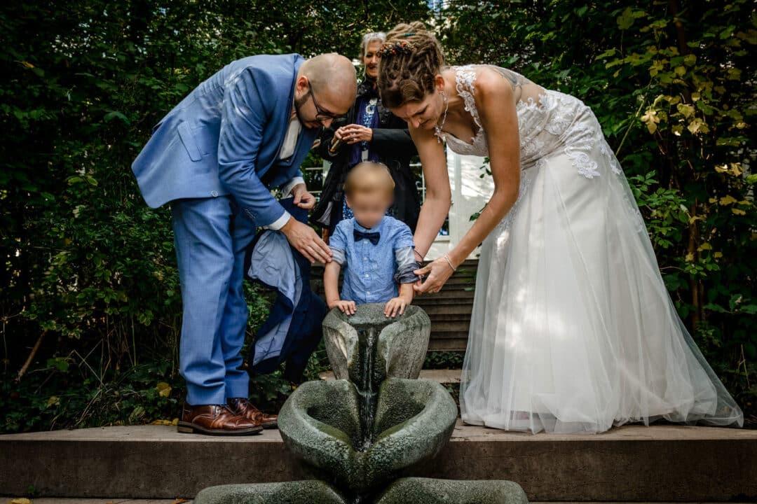 Braut und Bräutigam krempeln Sohn die Ärmel hoch