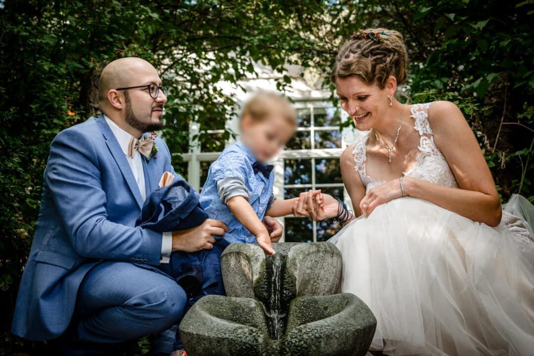 Braut und Bräutigam sitzen vor Wasserfallinstallation und schauen ihrem Sohn zu