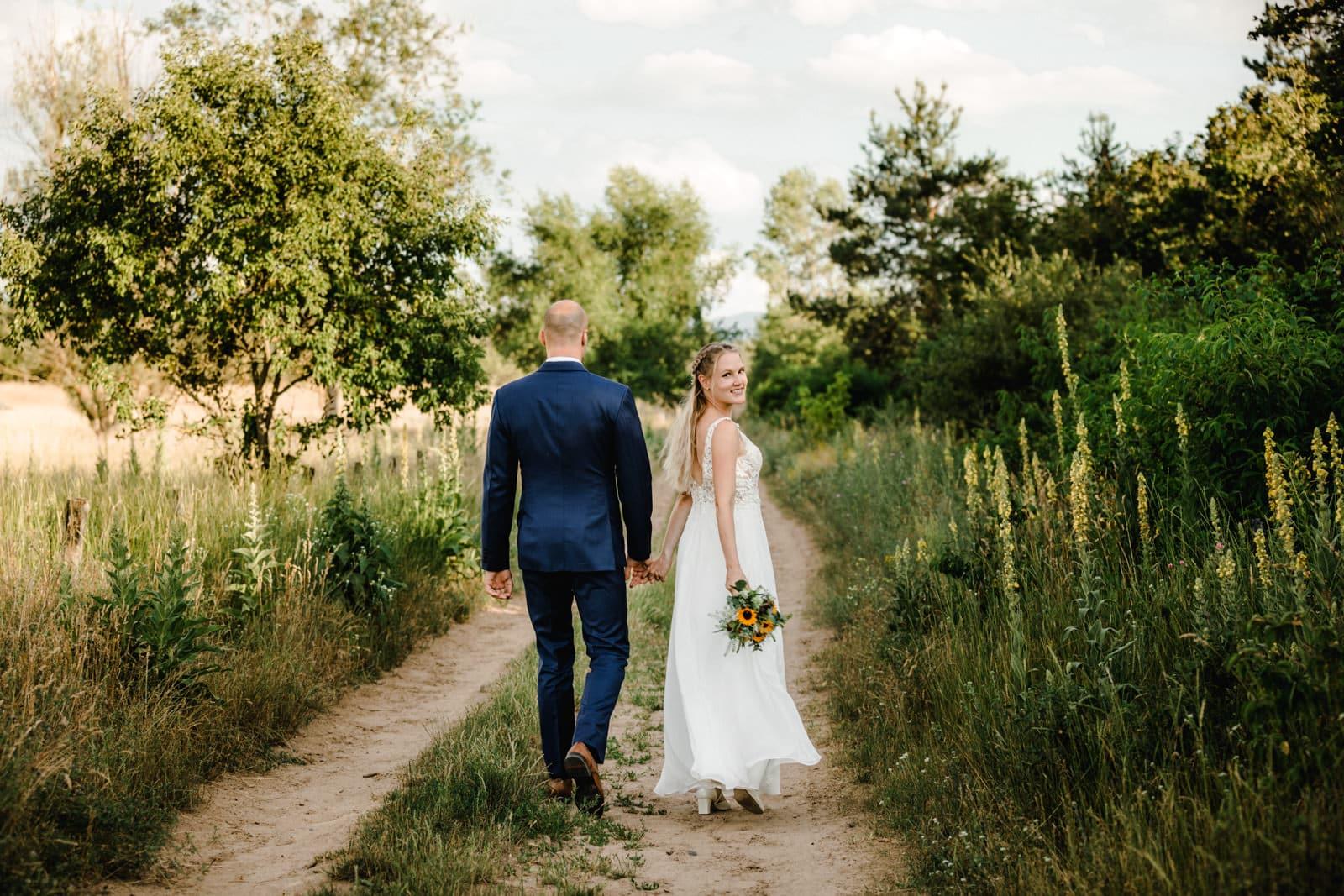 Brautpaar läuft Hand in Hand auf Feldweg im grünen entlang.