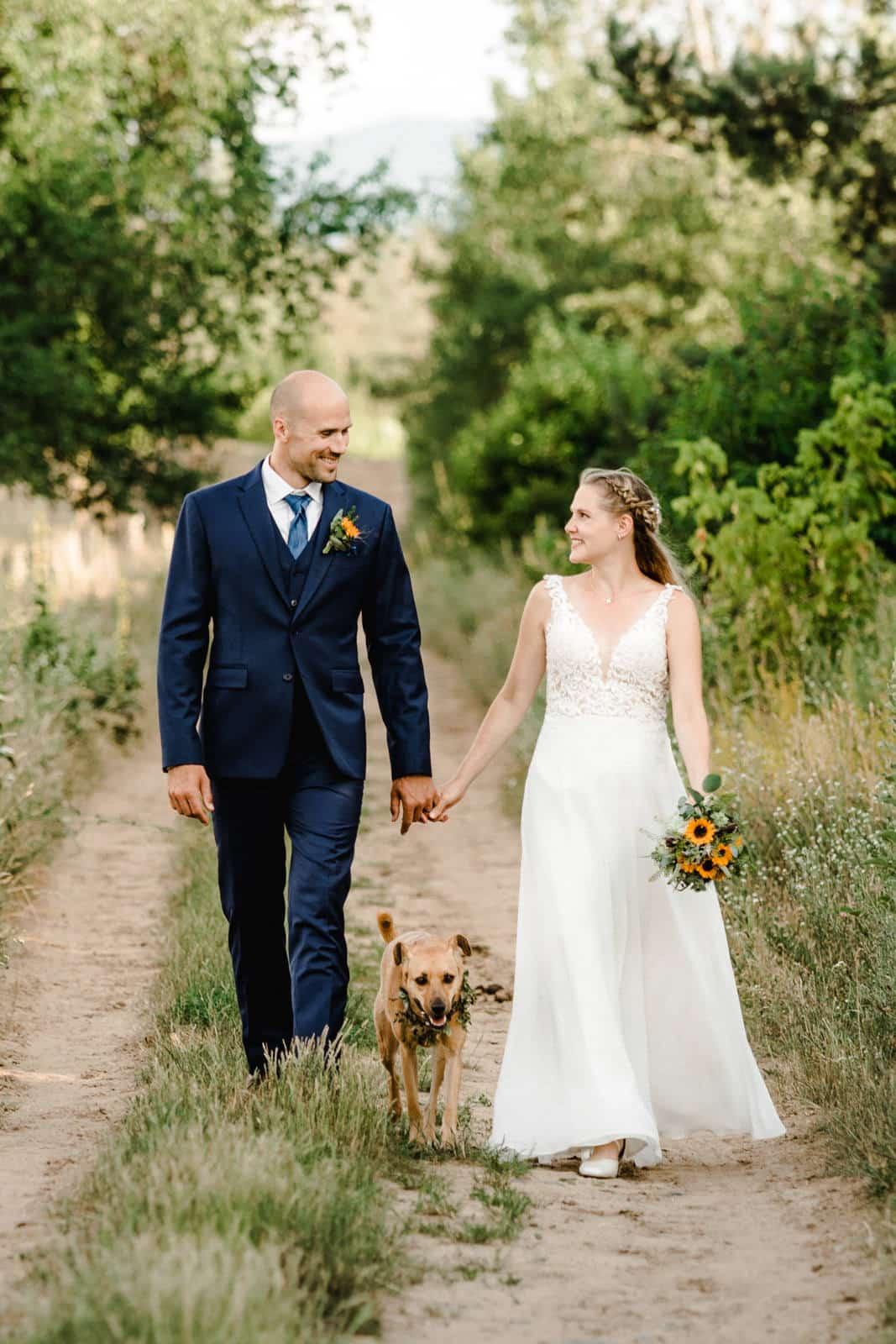 Brautpaar läuft in den Griesheimer Dünen mit ihrem Hund Hand in Hand einen Weg entlang im grünen.