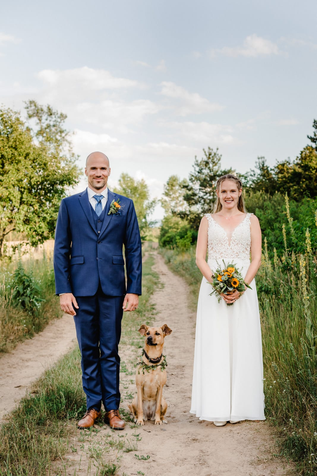Brautpaar steht in Griesheim in den Dünen gerade zur Kamera blickend da und ihr Hund sitzt zwischen Ihnen in der Natur.