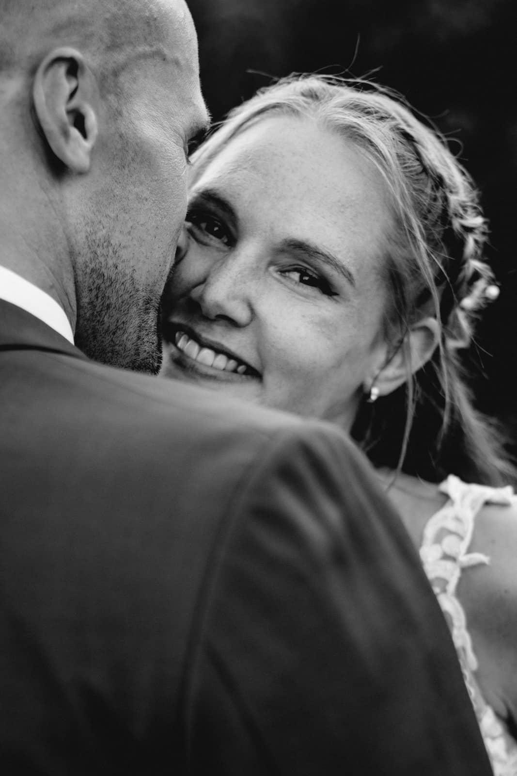 Braut schaut in die Kamera während sie sich an das Gesicht ihres Mannes anschmiegt.