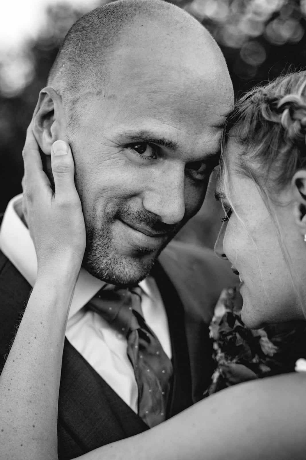 Bräutigam schaut in die Kamera während seine Frau mit ihrer Stirn an seine lehnt und ihre Hand an seinem Hals zärtlich angelegt hat.