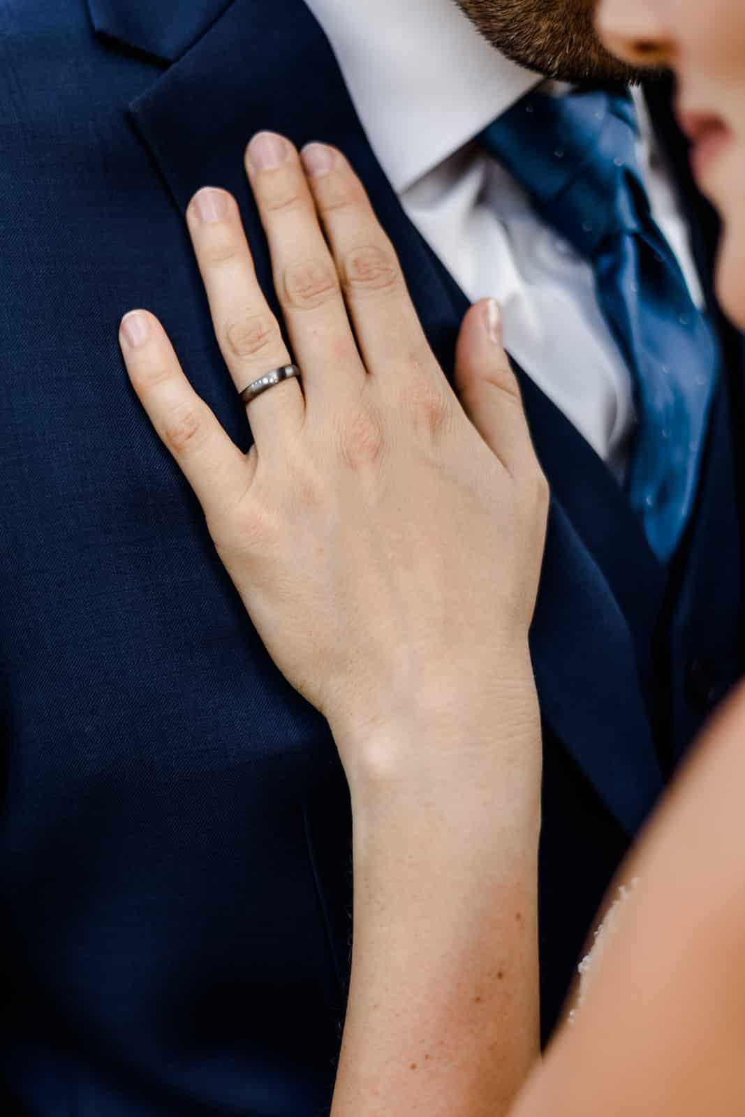 Nahes Fotos von Hand mit Ehering liegend auf dem Anzug des Ehemanns