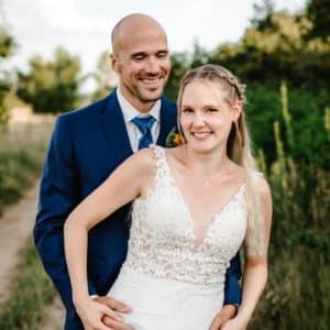 Braut lacht in die Kamera während ihr Mann hinter ihr steht und ihre Hände hält.