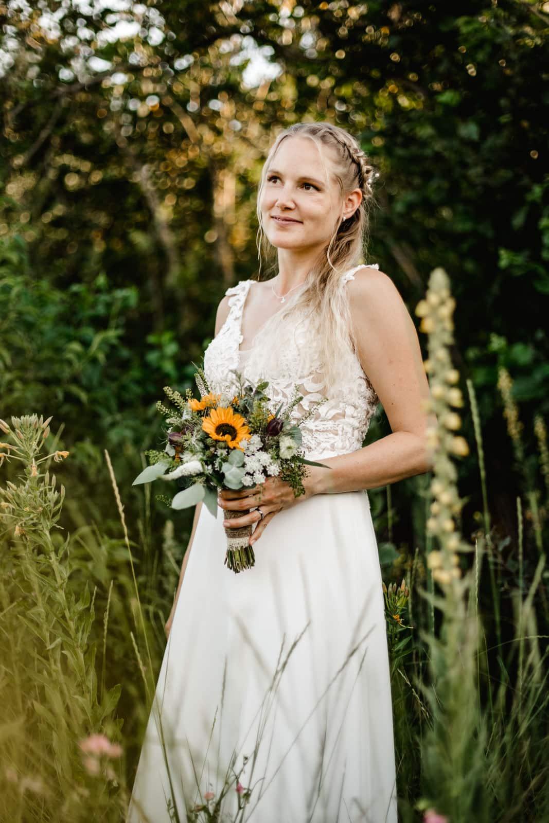 Braut steht in Wiese im grünen und hält Brautstrauss und lacht im Vintage Kleid