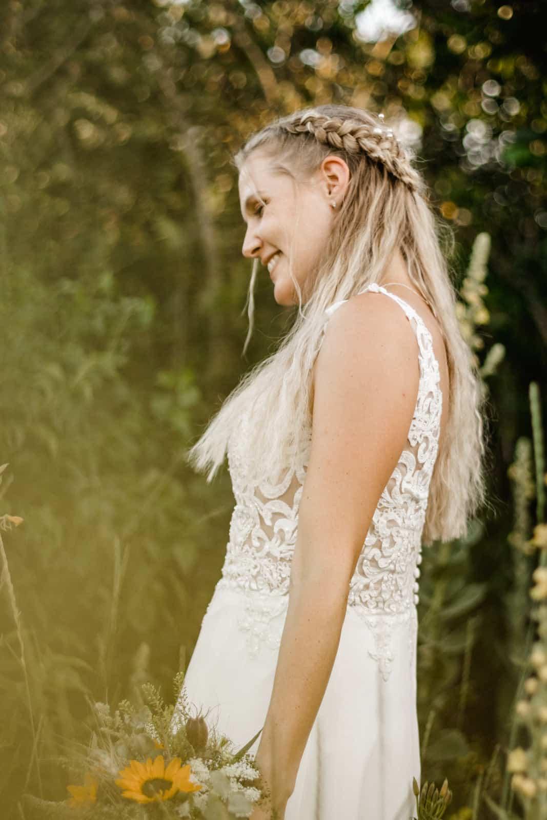 Braut lacht beim Fotoshooting im grünen und dreht sich dabei weg
