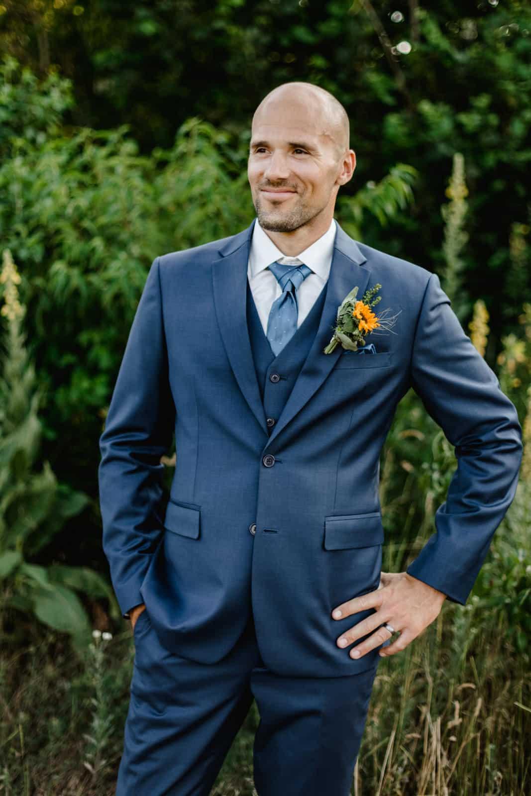 Bräutigam steht im grünen im Hochzeittsanzug mit Hände in den Hüften und lächeld