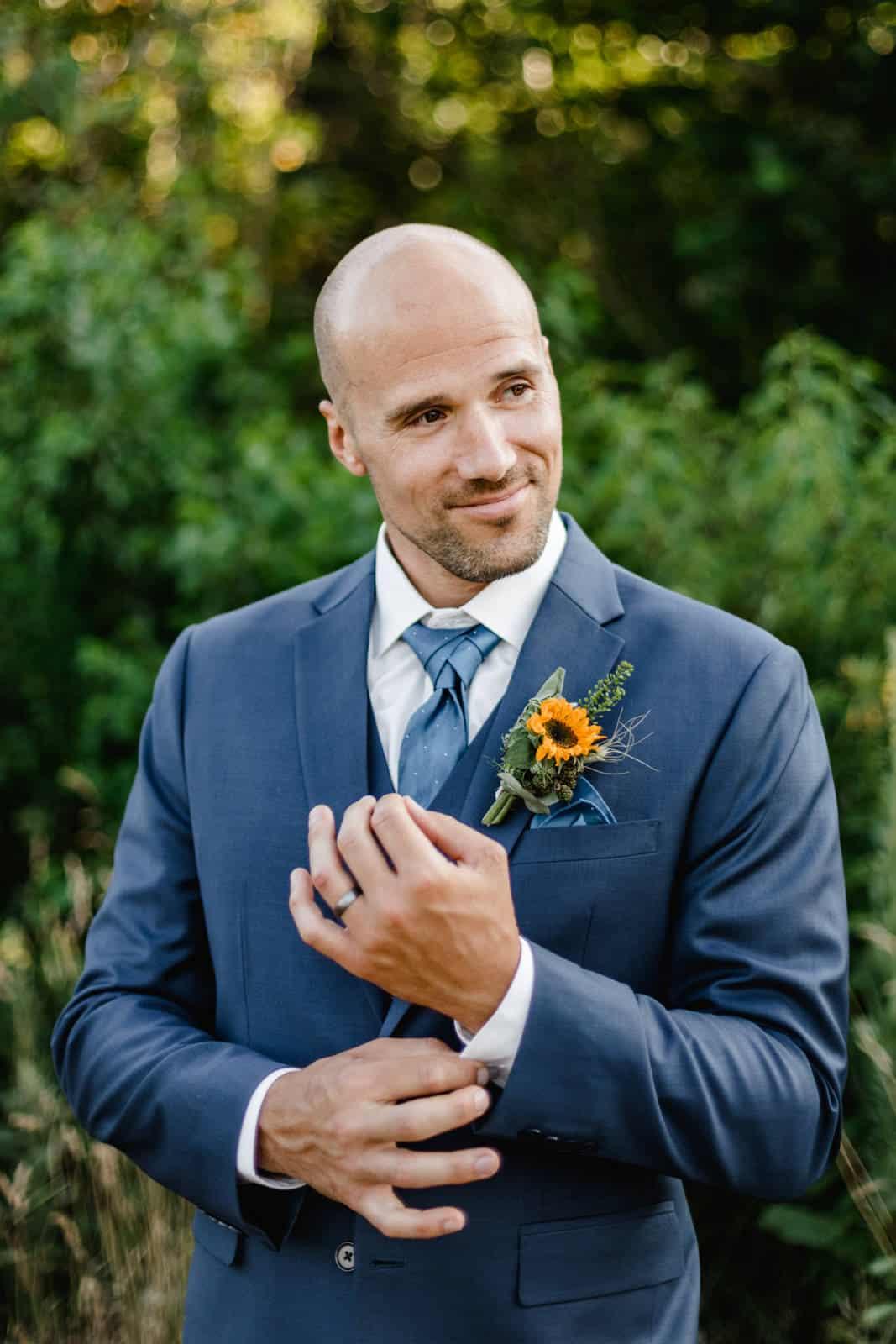 Bräutigam hält seinen Hemdsärmel und lacht verliebt