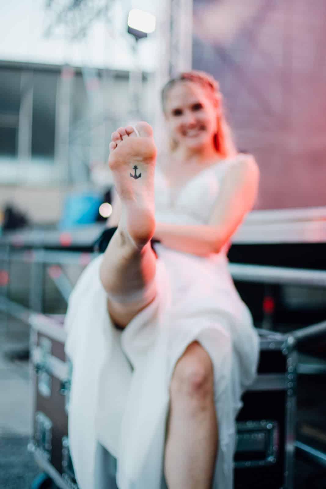 Braut hält Fuß in die Kamera worauf ein Anker tätowiert ist.