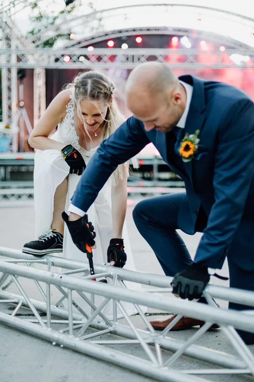 Braut steht mit einem Fuß auf einer Traverse während ihr Bräutigam eine Traverse freidengelt.